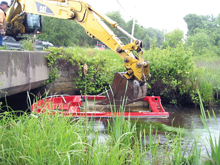 UP AND OUT: With the use of a backhoe, a city crew removed the abandoned boat Monday afternoon from the brook.