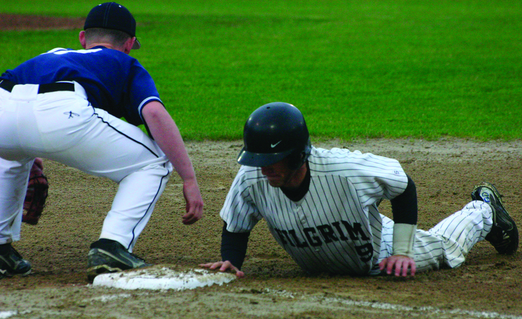 BACK TO THE BAG: Shawn Clayton slides safely into first base on a pick-off attempt during Monday's game.