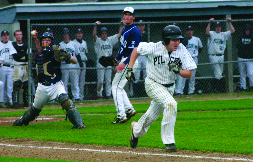 RUNNING WILD: Pilgrim's Colin Douglas heads for first as South Kingston catcher Chris Collins makes a throw in Monday's playoff game. Pilgrim rallied from a 10-4 deficit to win 11-10.