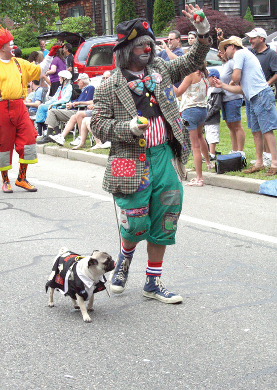 A Shriner, dressed as a clown, walks a pug.