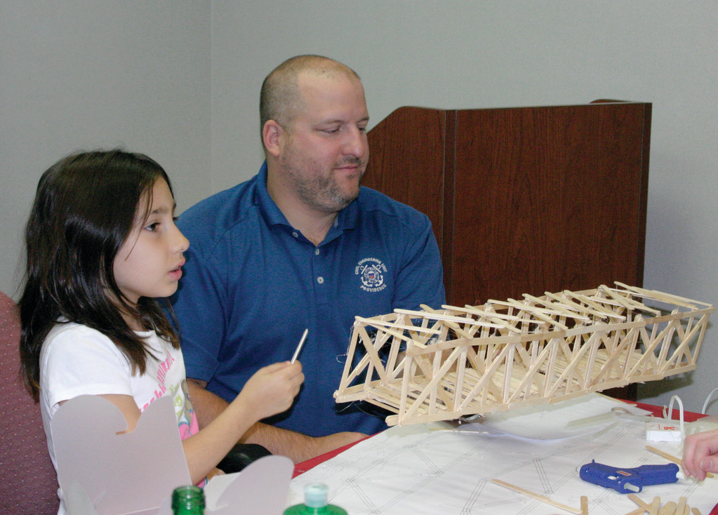 BUILDING MORE THAN BRIDGES: During a contest put on by the Rhode Island Mentoring Partnership and the Coast Guard Civil Engineering Unit Thursday, students from Randall Holden Elementary School learned the value of working together. Here, Josh Tessier of the Civil Engineering Unit assists second grader Jaelyn-Rose Cartagena, 7, with a bridge made from Popsicle sticks, dental floss and glue.