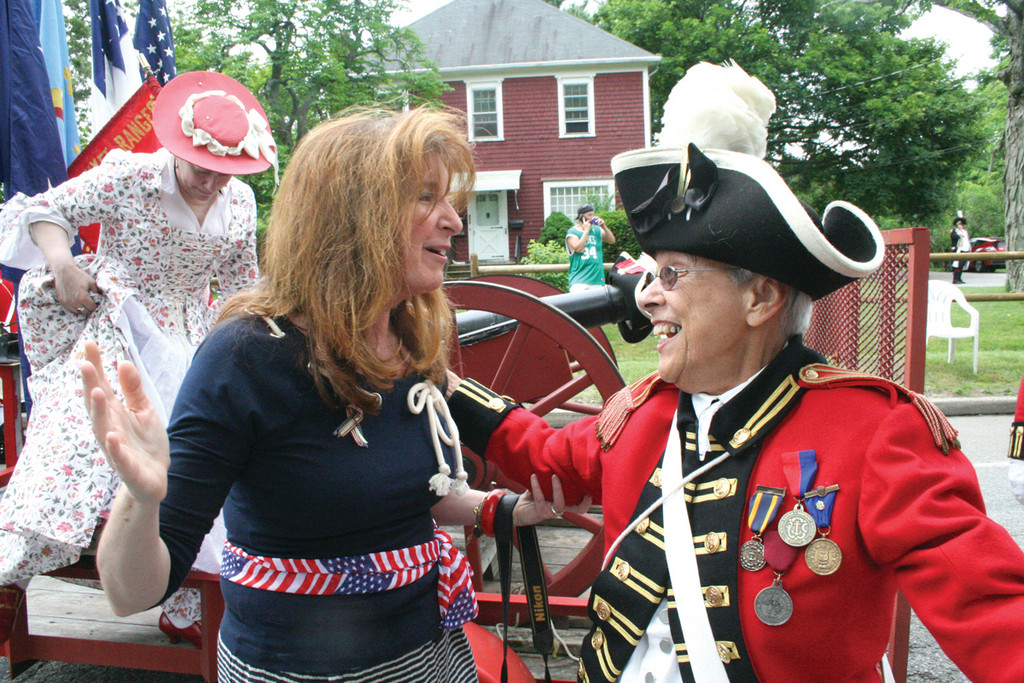 SEEING FRIENDS: Sue Stenhouse (left) and Jean Knowles, a member of the Pawtuxet Rangers, share a moment as parade divisions prepare to step off. This was Knowles' 37th parade.