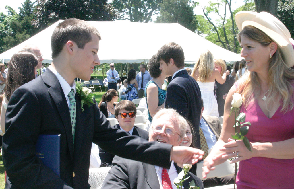 BEACON BUDDY: Ford Kelly-Riley, who did an internship at the Warwick Beacon this spring, hands his mother, Laurie Kelly, a rose as his father, Michael Riley, looks on. �He�s a good kid and we�re very proud of his accomplishments,� said Laurie. (Warwick Beacon photo by Jessica A. Botelho)