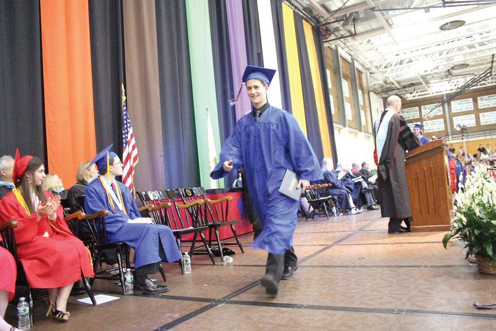 HE GOT HIS DIPLOMA: Toll Gate grad Ian Bouressa walks across the stage Thursday eveing.