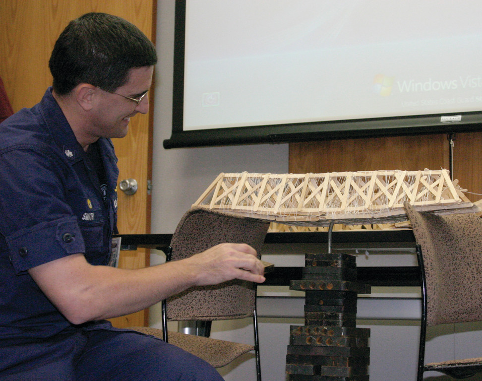 WORTH THE WEIGHT: The winning bridge, made by Cassidy Barker, 9, and her teammate, Sidney, 7, a first grader, sustained 82 pounds of weight. Commanding Officer Will Smith marvels at the strength of the Popsicle stick structure.