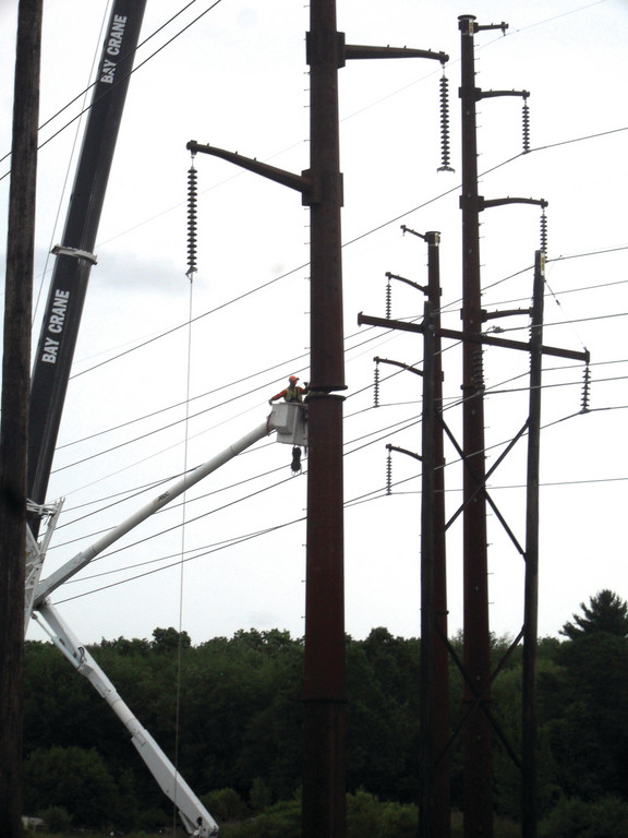 HANGING OUT: Crews lower half of a transmission tower to complete installation Tuesday in Smithfield.