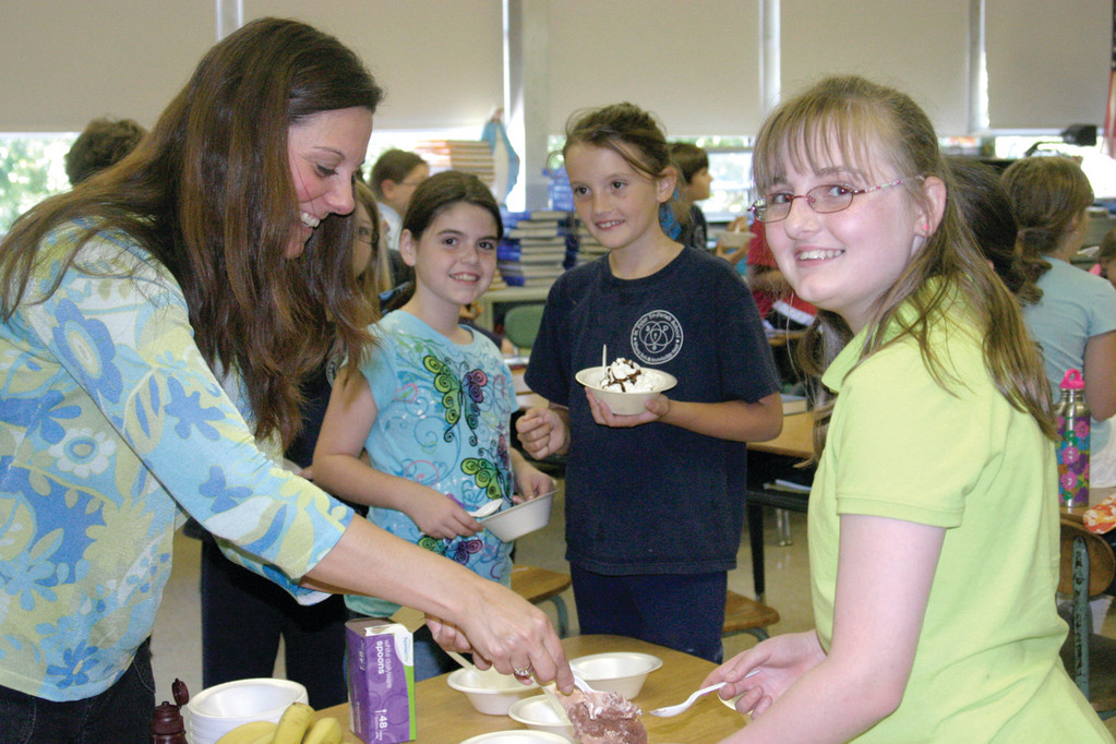 SCOOPS FOR RYAN: After seeing an event invitation on Facebook with more than 60,000 participants, Stephanie Kaczmarzyk decided to hold a banana split party at St. Peter's School to teach fourth graders the importance of living life to the fullest, as well as treating others with disabilities as equals. Here, she serves Haeleigh DeFeo, 10, as Marissa Birmingham, 10, and Alyssa Richard, 9, look on.