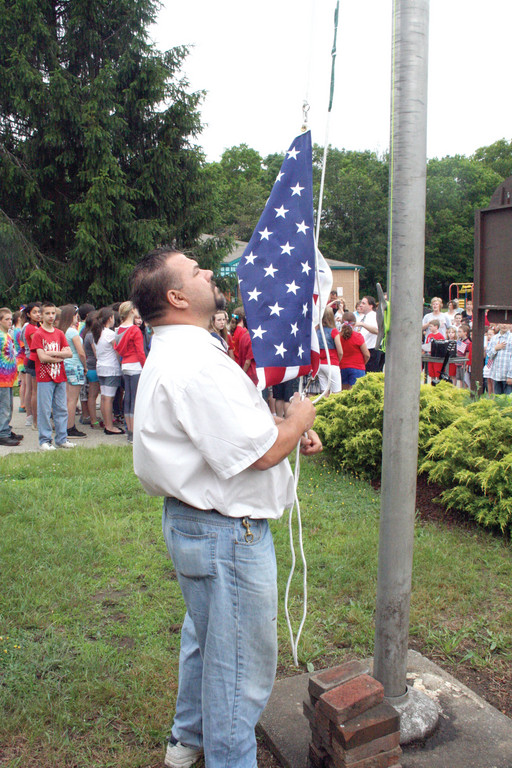 CUSTODIAN WITH A TIE: Richard Russo did the honors of raising the flag as the school sang the national anthem.