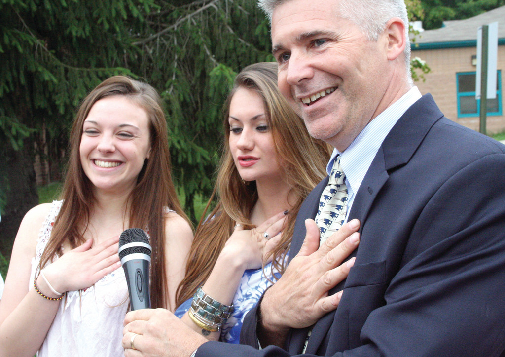 HONORARY CITIZEN: Erin Clarke (far left) of Australia lead the school in the Pledge of Allegiance. She is pictured with Hoxsie Principal Gary McCoombs and his daughter, Kayla. Erin and Kayla became friends while attending a school in Vienna, Austria.