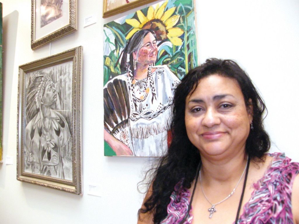 ART AND ARTIST: Deborah Spears Moorehead poses in front of her wall of art, a collection of sketches and paintings on canvas and wood, at the Rhode Island Department of Administration. Her art is being displayed as part of the first ever Native American art exhibit at the building, a gallery showing Moorehead curated.
