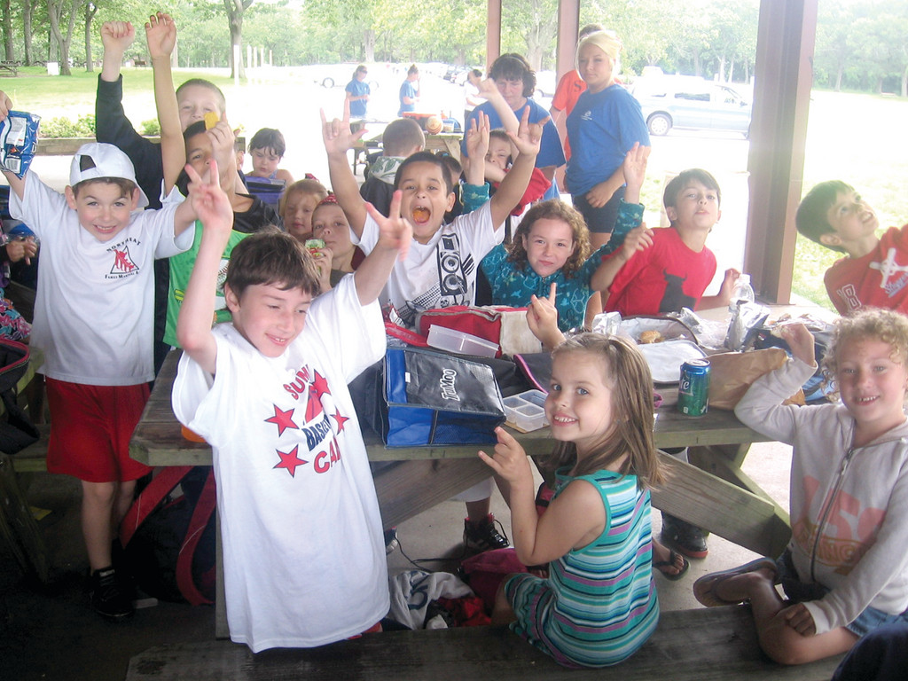 """SO HAPPY TOGETHER:"" Many of the 96 children taking part in the Boys and Girls Club summer camp at the Masonic Youth Grounds in Buttonwoods say being together is their favorite aspect of camp. Here, children enjoy lunch on the first day of camp."