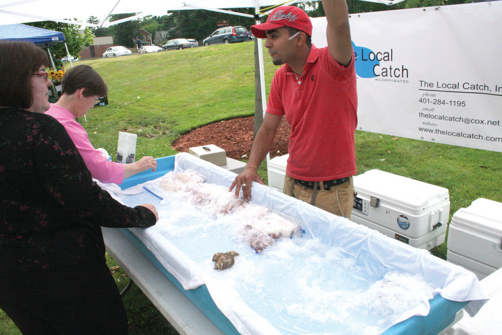 FRESH FROM RHODE ISLAND WATERS: The Local Catch Inc. was just about cleaned out within the first two hours of the Pawtuxet Farmers' Market last Saturday. Here, Joe Blum talks with a customer, providing information not only on how the fish might be prepared but where it was caught.