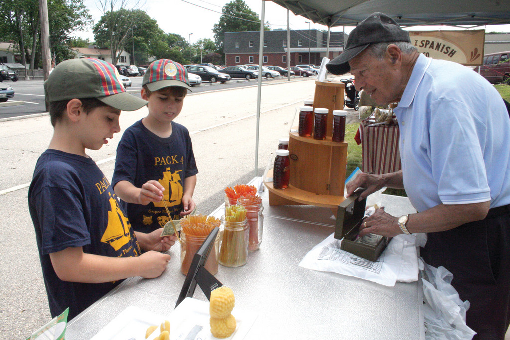Harry Dolan and Jim Hart sample different honeys at Bernard Bieder's display tat the farmers' market held Saturday morning at the Rhode on the Pawtuxet parking lot.