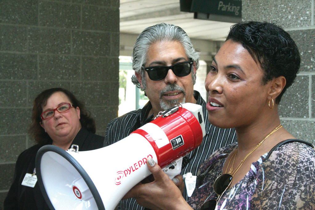 GLAD FOR AIRPORT EXPANSION: Celeste Ramos, a janitor at Green Airport, addresses fellow union members at a rally Thursday as Ward 3 Councilwoman Camille Vella-Wilkinson and Scott Duhamel, secretary treasurer of the Rhode Island Building Trades Council, look on.