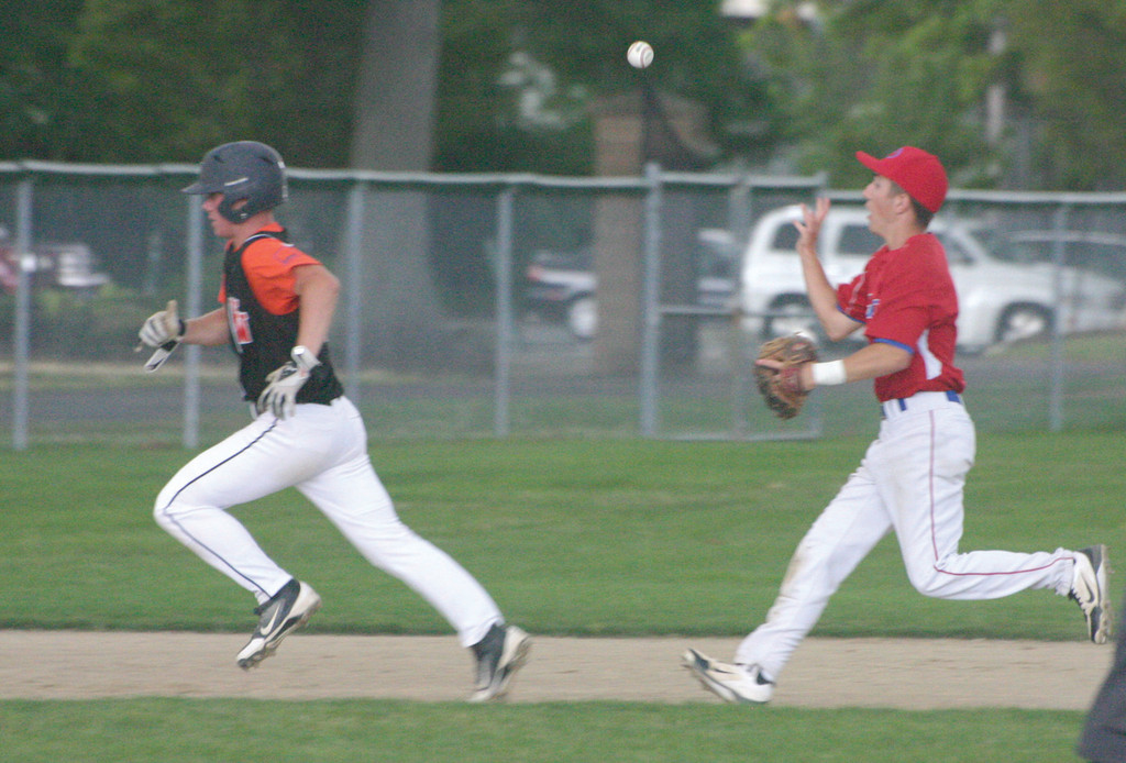 Ron Gaynor flips to third as West Warwick's Ray Zincone head for the base.