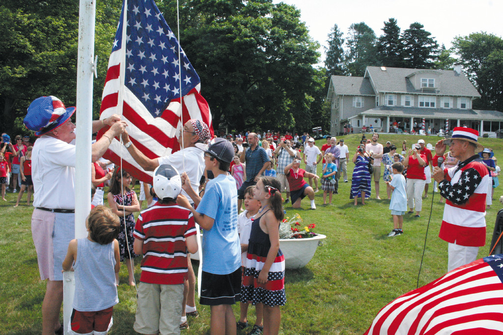 A JULY 4TH TRADITION: Parade participants and spectators joined on Nixon's lawn overlooking Greenwich Bay to salute the flag.