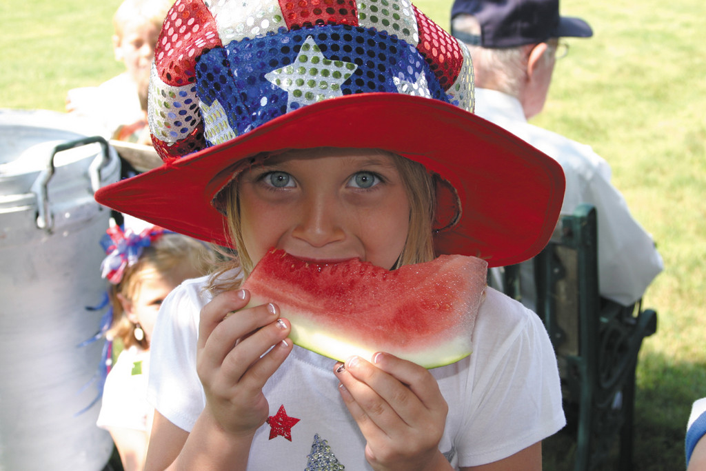 SWEET SNACK: Bella Redkey, 6, of Vermont, savored a slice of watermelon at the waterfront home of Bill Nixon, who invited friends and neighbors to his house for the raising of the American flag followed by watermelon, cookies and lemonade.