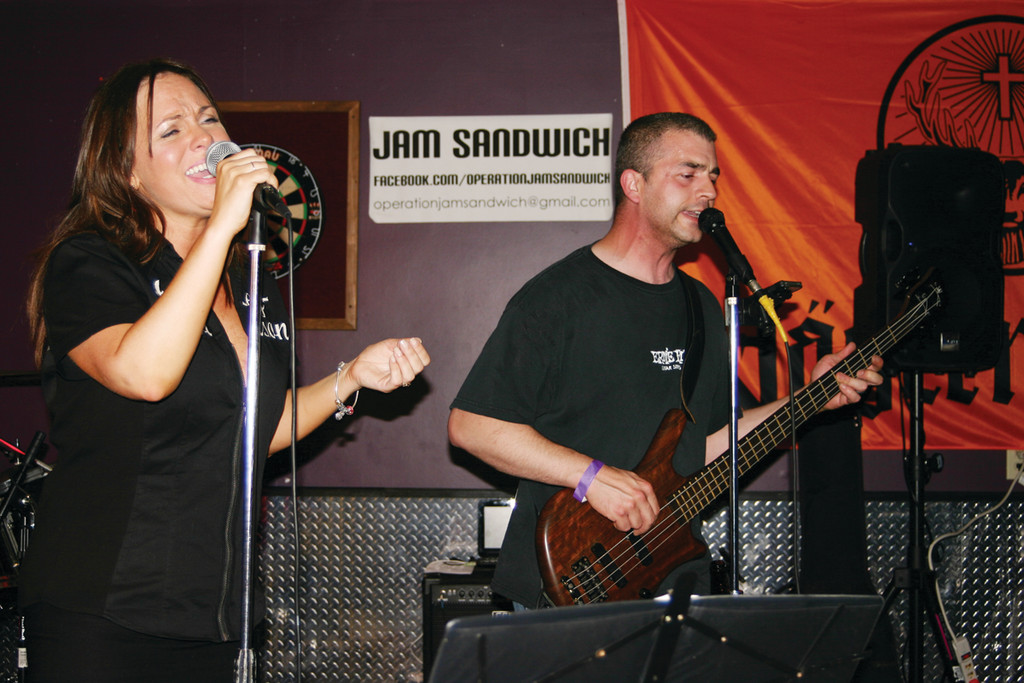 "JAM SANDWICH: The rock band Jam Sandwich performed at the fundraiser. Lead vocalist Kelley Erickson and bassist Joe Napolillo belt out a Rolling Stone song, ""Gimme Shelter."""