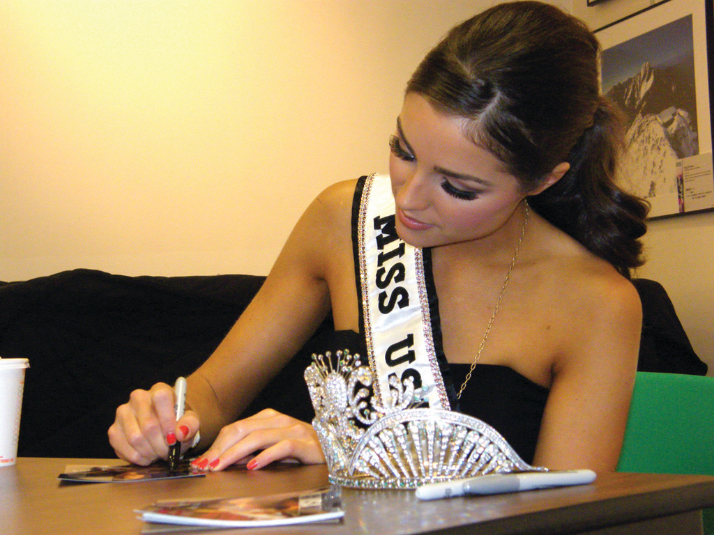 WITH HER CROWN: Miss USA signs autographs for youngsters at the Cranston Public Library.