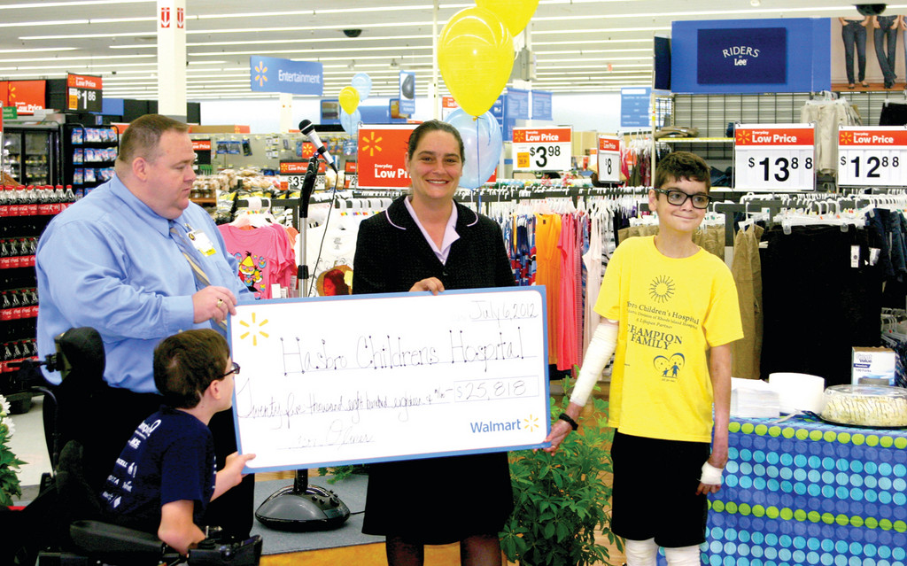 INSPIRING A COMMUNITY: Wal-Mart store manager Jason Olivier (left) and assistant manager Alexis Tulli (center left) cut a check to Hasbro Children�s Hospital, care of Evan Hudson (bottom left) and Tony Torres (right), who inspired the store and the community it supports to raise over $25,000 for the hospital.