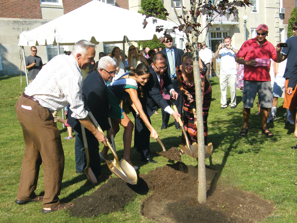 "SMILES AND SHOVELS: From left, Peter Culpo, Cranston City Council President Anthony Lupino, Miss USA Olivia Culpo, Cranston Mayor Allan Fung and Susan Culpo scoop shovelfuls of dirt and ""plant"" a tree in Olivia's honor in front of Cranston City Hall."