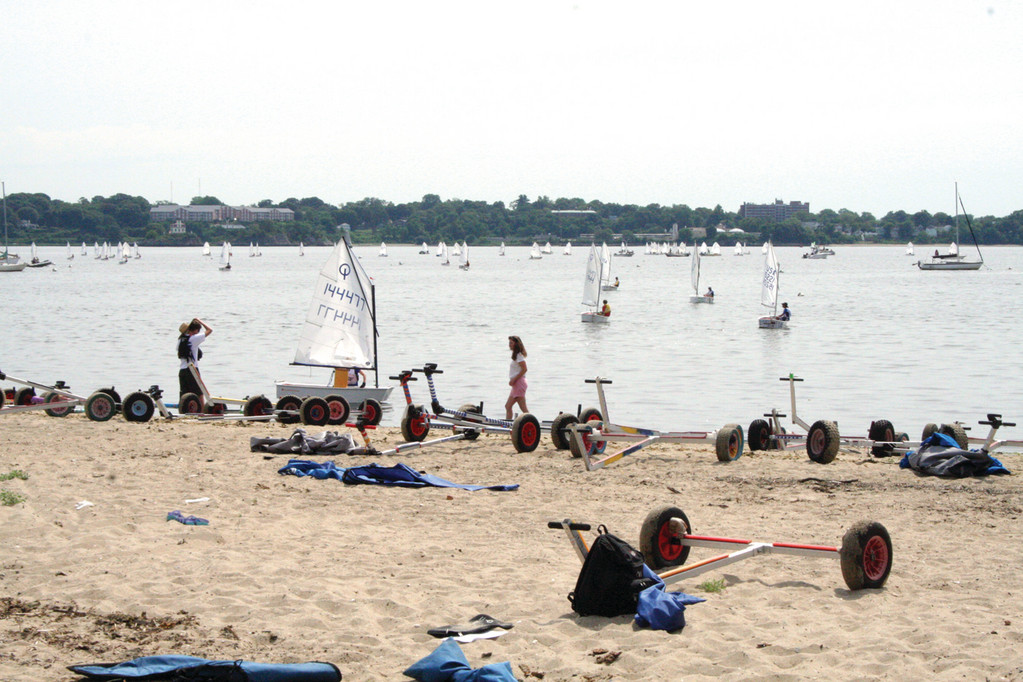 ON THE BEACH: Opti sailors head out to the course, leaving trailers in their wake on the beach.