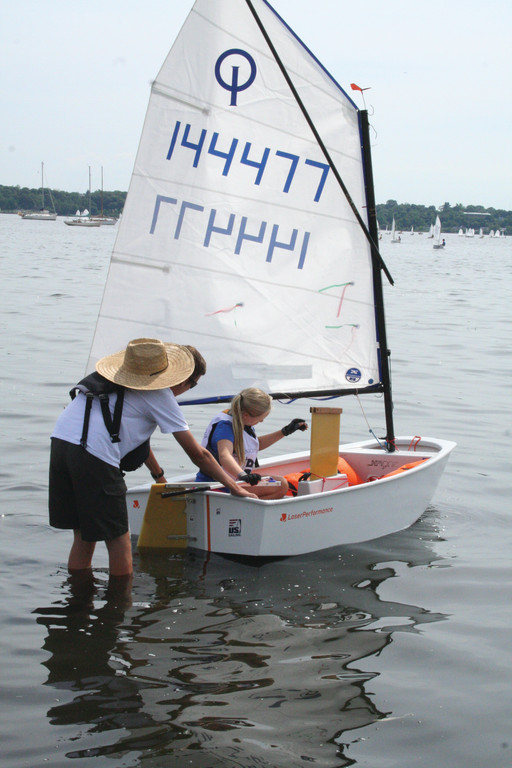 OFF TO THE RACES: Conanicut Yacht Club coach Jamie Reynolds helps launch a competitor from the beach at the Edgewood Yacht Club.