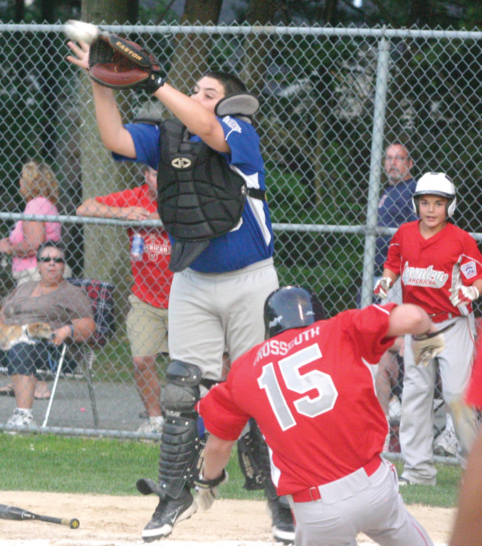 LEAPING: National's Kyle Denis jumps to catch a throw as Coventry American's Jarrad Grossguth slides in during Monday's game. Grossguth was safe, and Coventry held off National 7-5.