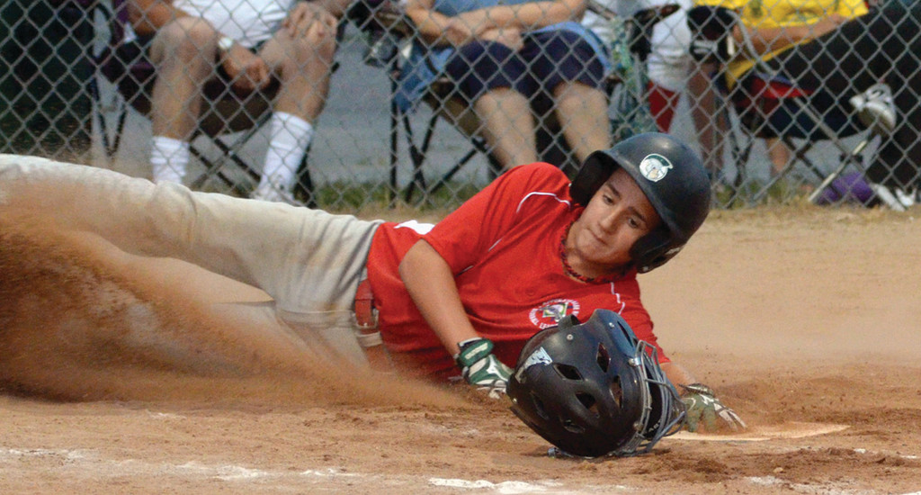 SAFE AND SOUND: Apponaug's Josh Coleman slides into home plate during Tuesday's winners' bracket final in the 12-year-old Cal Ripken state tournament. Apponaug beat Cranston Power CLCF for a spot in tonight's championship.