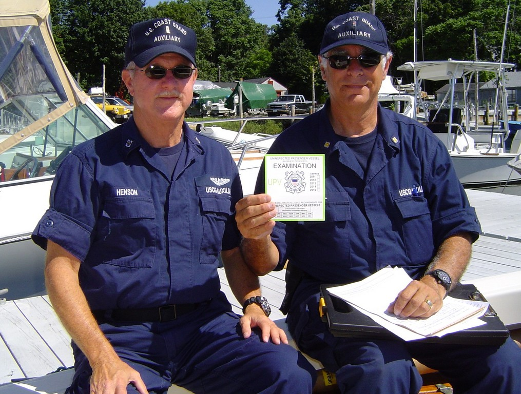 Doug Henson (left) and David Siesel of the U.S. Coast Guard Auxiliary (North Star Flotilla, Warwick) issue an Uninspected Passenger Vehicle (UPV) examination sticker to the charter boat Angel Light.