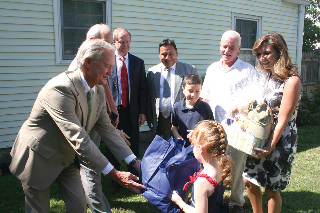 HOME SWEET HOME: Governor Lincoln Chafee hands over several gift baskets to the McGuire family at a press conference at their house last Thursday.