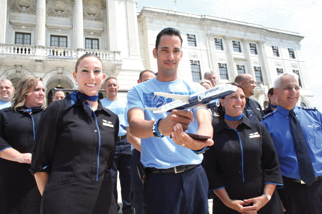 SEEING BLUE: Joined by other JetBlue employees living in Rhode Island, Chris Alvarez holds a model plane that was later presented to Governor Chafee during yesterday's announcement.