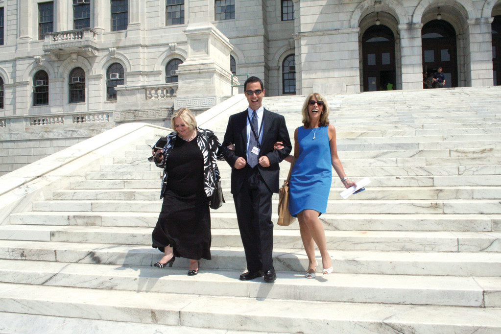 ESCORT: Brian Schattle, CFO for the Rhode Island Airport Corporation, accompanies Sharon Traficante (left) and Patti Goldstein, RIAC vice president of marketing, down the State House stairs prior to the start of the ceremony. More than one speaker credited Goldstein's persistent efforts to helping bring JetBlue to Rhode Island.