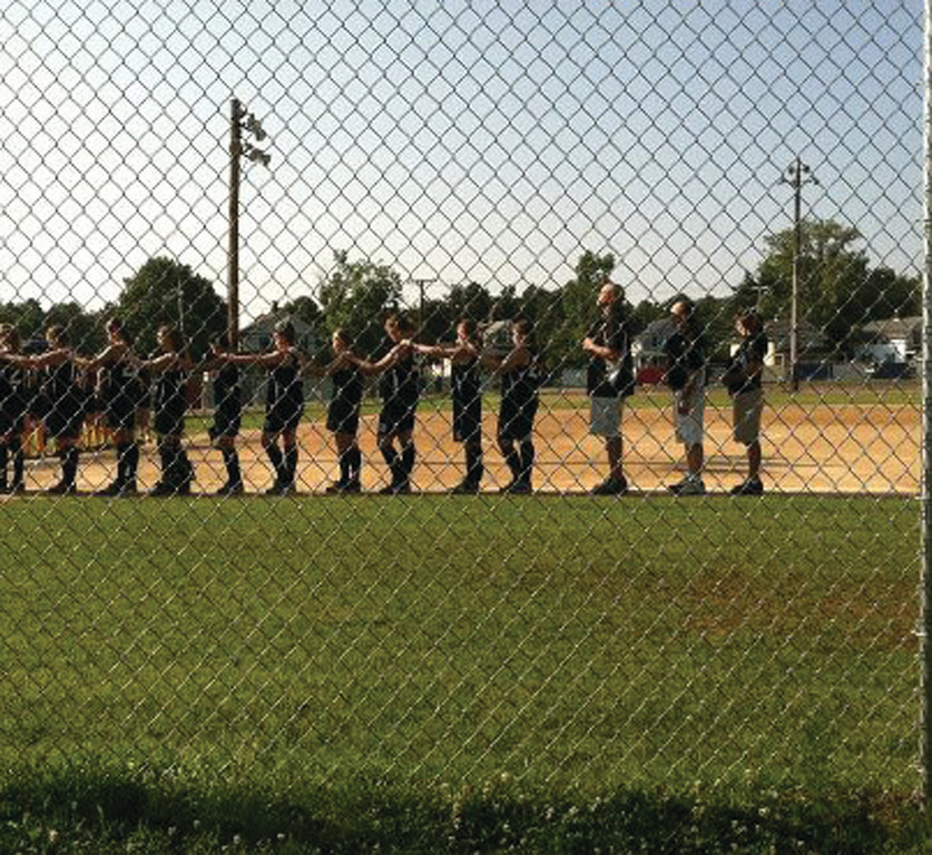 WAITING IT OUT: The Warwick West Side senior all-star softball team listens to the National Anthem before one of its games in the state tournament over the weekend.