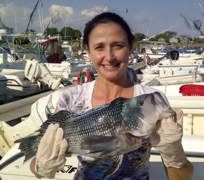 Suzanne Sustello with a nice black sea bass she caught off the center wall at the Harbor of Refuge when fishing with her husband Rick last week.