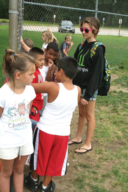 WAITING FOR A TURN: Camp counselor in training Jenna Daigle chats with Group 2 campers as they wait for their turn at bat.
