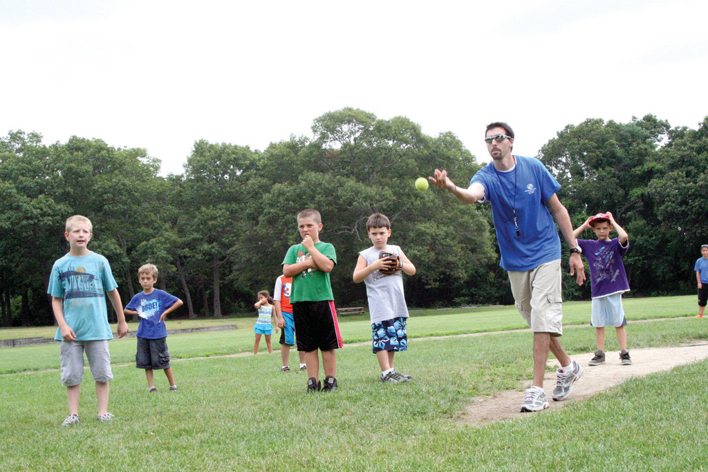 MAN ON THE MOUND: With a closer of kids anxious to play a role in the game, counselor William McGovern pitches.