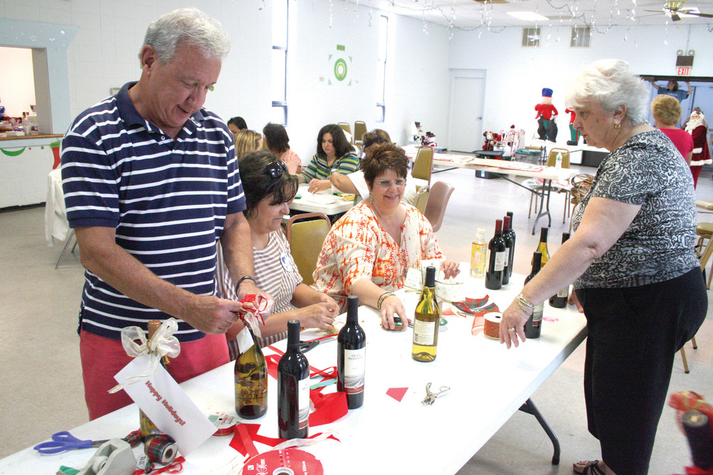 PRETTY BOTTLES: Dr. Stewart Rosenfeld of Koch Eye Care decorates wine bottles that were sold at the imPossible Dream Christmas in July fair held Saturday.