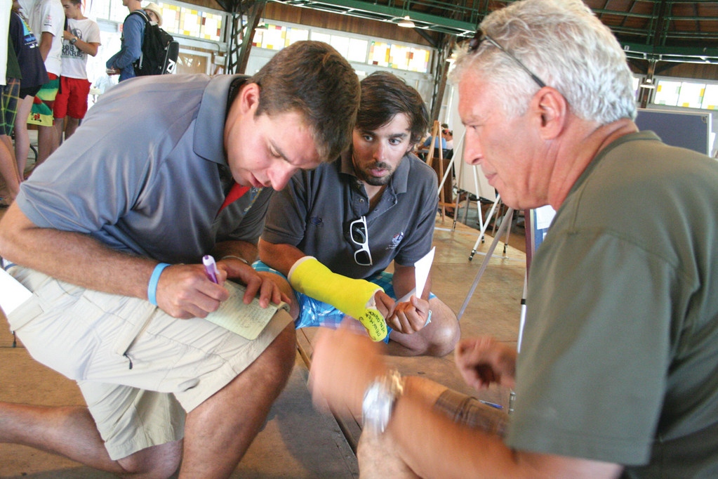 GETTING DOWN THE DETAILS: Justin Assad and his brother Kyle, who with other friends of CJ started the regatta, check over event details with John Langella, a regatta volunteer for years.