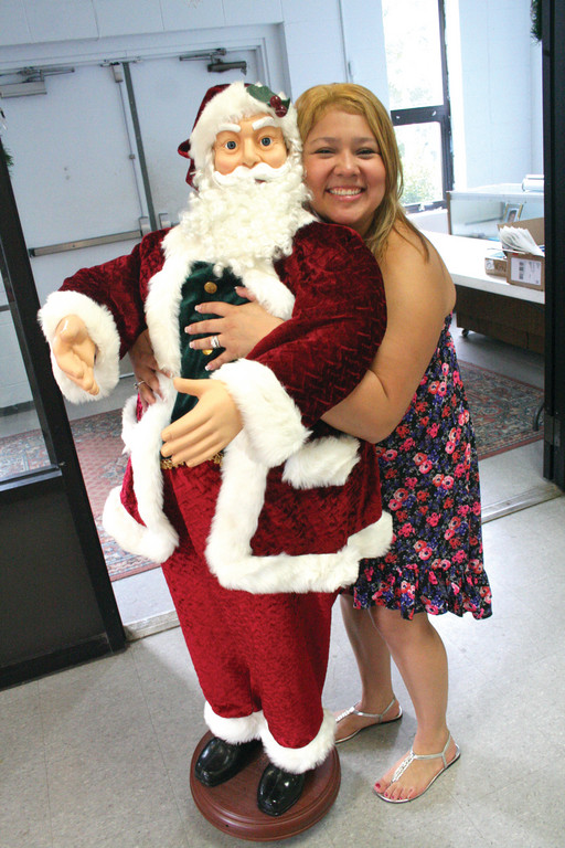 LOVING CHRISTMAS: Cristy Reyes hugs one of the Christmas elves that helped create the Christmas in July theme at the imPossible Dream.