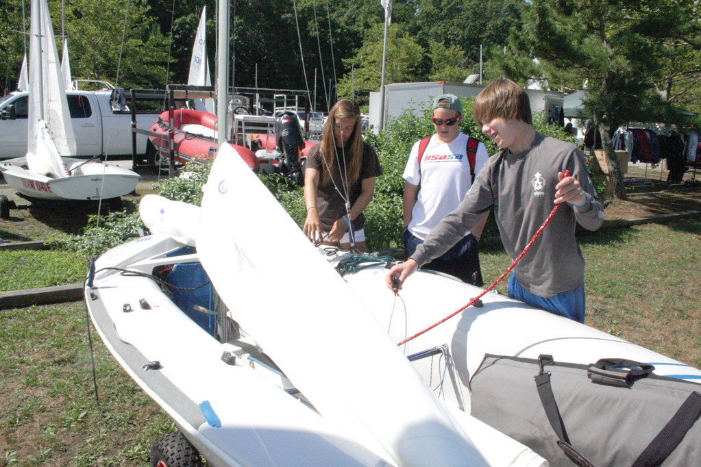 PREPARED TO RACE: Sailors from left: Riley Legault, Tommy Garber and Max Simmons rig their boat.