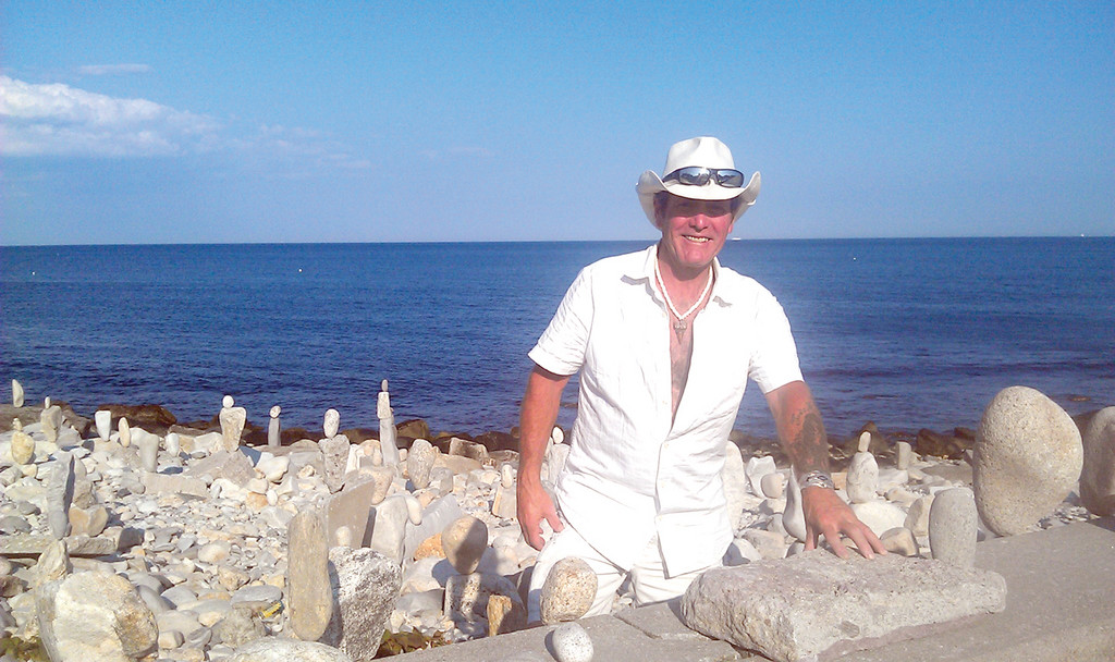 "ROCK STAR: Joseph DiPietro, known to his friends and family as ""J.D. Mystery,"" enjoys creating rock art at local beaches, as well as remodeling homes with recycled products. Here, he smiles with his rock art at Narragansett Beach."