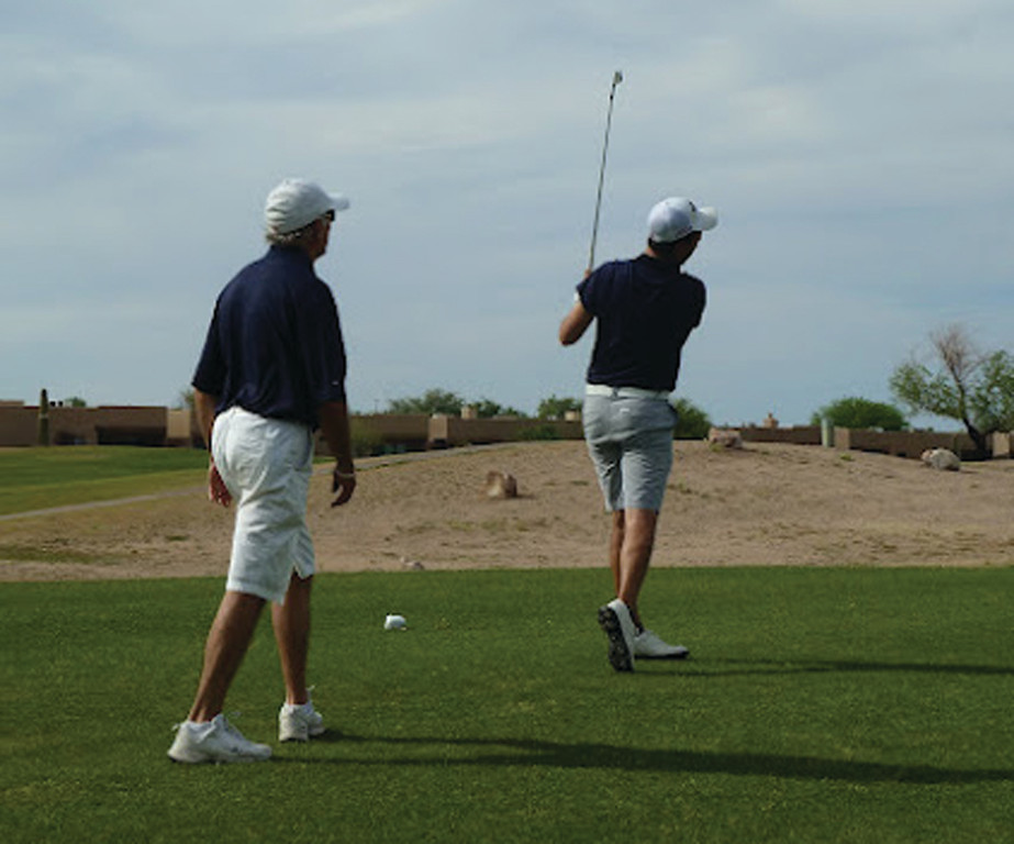GETTING IT DONE: A blind golfer follows his swing while his coach watches the shot.