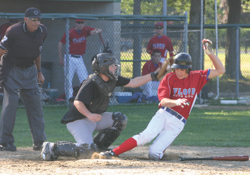 SAFE: Flood's Kevin Sutyla just gets under the tag to score a run in Monday's Connie Mack playoff opener.