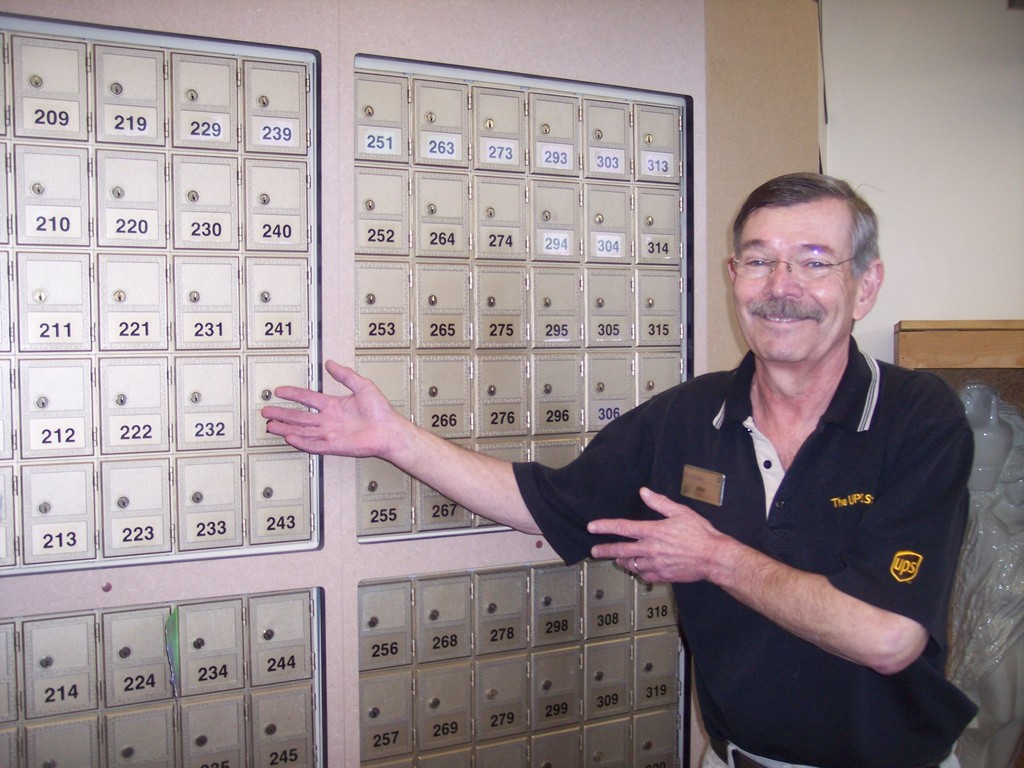 Meet Ken, showcasing the wall of mailboxes available for rent at The UPS Store in the Gateway Plaza in Warwick.