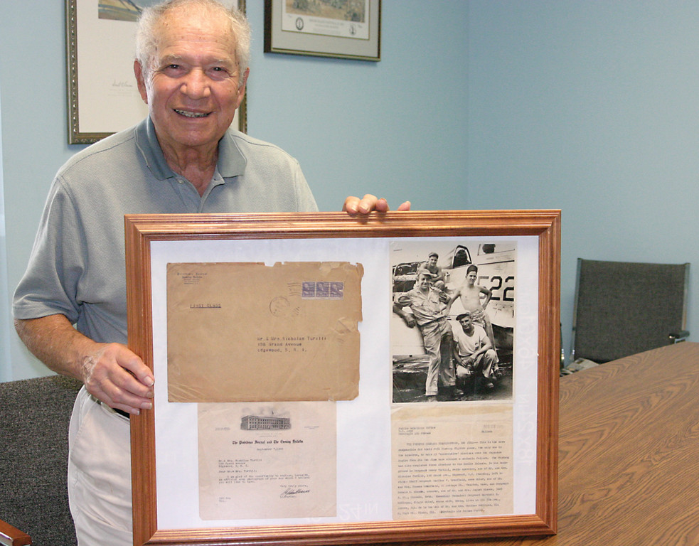 HONORABLE VETERAN: World War II veteran Dewey Turilli, 89, remembers his time in Iwo Jima vividly as a radio operator in the Air Force. He holds up a framed document that was sent to his parents during the war as his crew were the only one in their squadron to make 15 consecutive missions above the Japanese Empire from its Iwo Jima base without a mechanical failure in a P-51 Mustang fighter plane.
