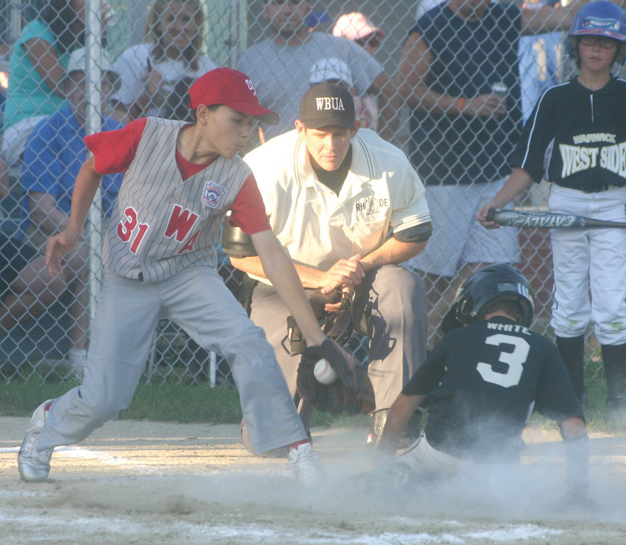 West Side's Jake White slides into home on a wild pitch as American's Devin Budlong covers the plate.