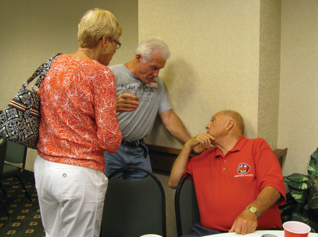 Ray Clearwater (center), a former pro hockey players who starred in 214 NHL games, explains some phases of his famed career with Dick Bartlett (right), a Warwick resident an Reds Society board member, at last Friday evening's special social at the Hampton Inn & Suites Hotel on Post Road as his wife Judy looks on.