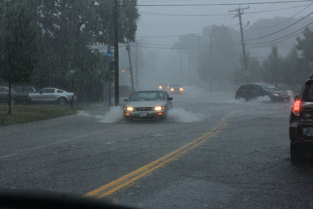 Cars make their way down a flooded West Shore Road on Friday.