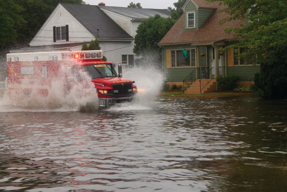 MAKE WAY: An ambulance attempts to make its way through the flooded neighborhood near the intersection of Archdale Avenue and West Shore Road on Friday.